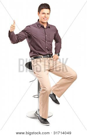 A young man sitting on high chair and giving thumb up isolated on white background