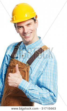 Smiling young happy builder worker in protective hardhat and workwear overall with thumb up isolated