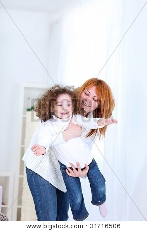 Happy mother playing with her baby at home