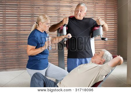 Three senior people talking in gym while having a break