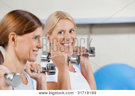 Two happy senior women exercising in gym with dumbbells