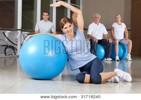 Happy woman doing back exercises with blue gym ball in fitness center