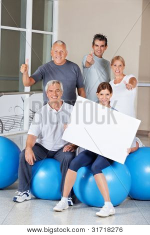 Senior citizens on gym balls holding empty advertising sign in fitness center