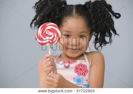 Portrait of Asian girl with ponytails holding sucker