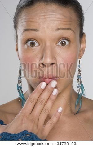 Portrait of shocked woman with fingers on mouth