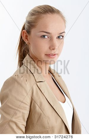 Smiling blonde girl portrait with ponytail, looking at camera, studio.