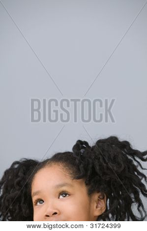 Portrait of Asian girl with ponytails looking up