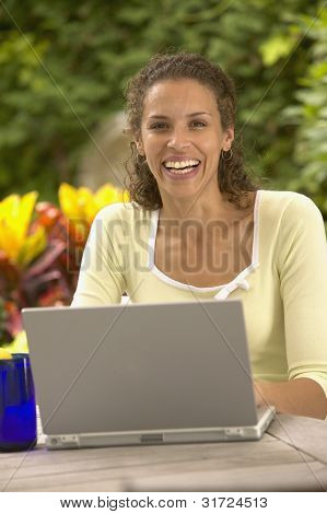 Portrait of woman sitting at table with laptop