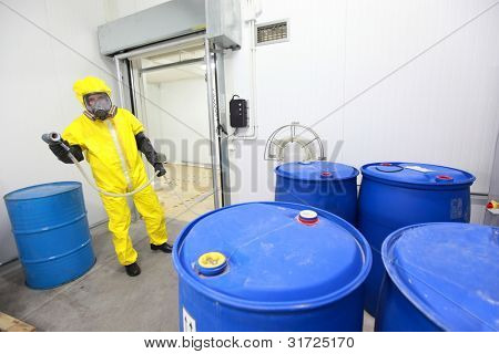 Fully protected in yellow uniform,mask,and gloves professional dealing with barrels with toxic wastes