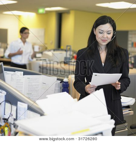 Businesswoman reading paper in office