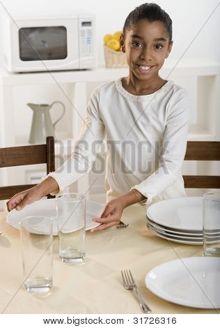 Girl setting kitchen table