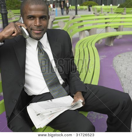 Businessman with newspaper talking on cell phone
