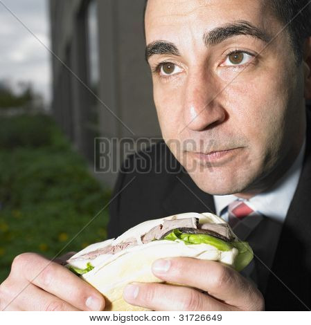 Close up portrait of businessman eating sandwich