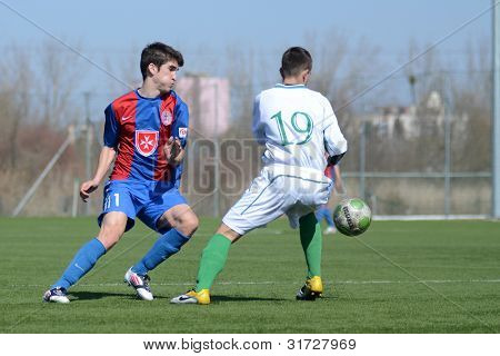 KAPOSVAR, HUNGARY - MARCH 17: Richard Csaki (white) in action at the Hungarian National Championship under 18 game between Kaposvar (white) and Videoton (blue), March 17, 2012 in Kaposvar, Hungary.