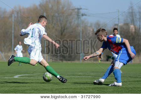 KAPOSVAR, HUNGARY - MARCH 17: Attila Kovacs (white) in action at the Hungarian National Championship under 18 game between Kaposvar (white) and Videoton (blue), March 17, 2012 in Kaposvar, Hungary.