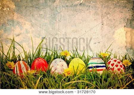 Grunge paper with Easter Eggs and flower on Fresh Green Grass over blue sky