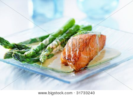 Salmon fillet with asparagus and yellow sauce in horizontal orientation