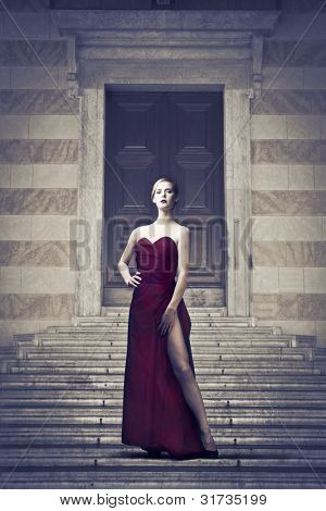 Beautiful elegant woman in front of a luxury palace