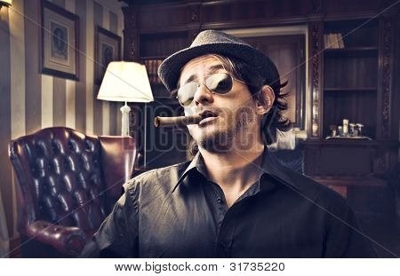 Young gangster smoking a cigar in a luxury studio