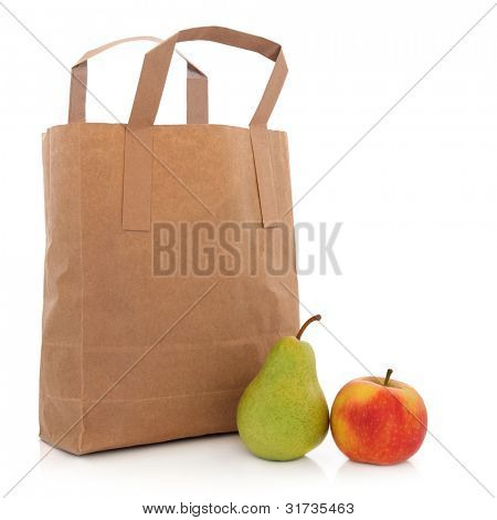 Recycled brown paper carrier bag with apple and pear over white background.