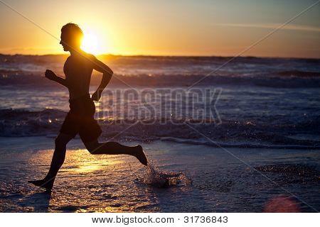 Hombre corriendo en la playa al atardecer