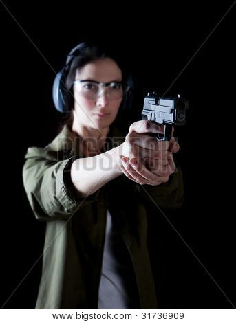 Woman aiming a gun with protective gear
