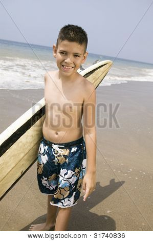 Portrait of boy holding surfboard on beach