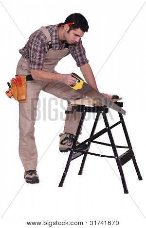 Handyman sawing a plank of wood