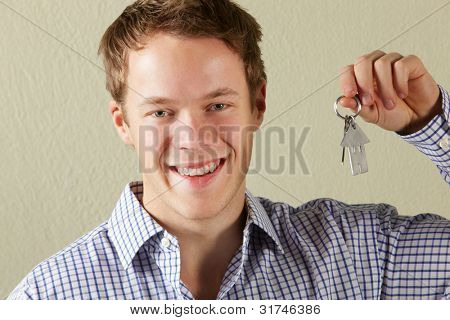 Studio Shot Of Young Man Holding Keys To First Home