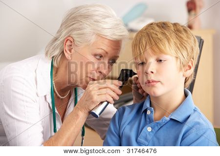 British GP examining young boy's ear
