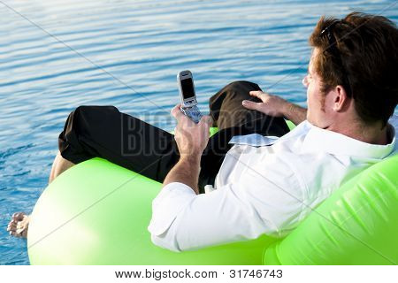 Young man relaxing on the pool, using mobile phone