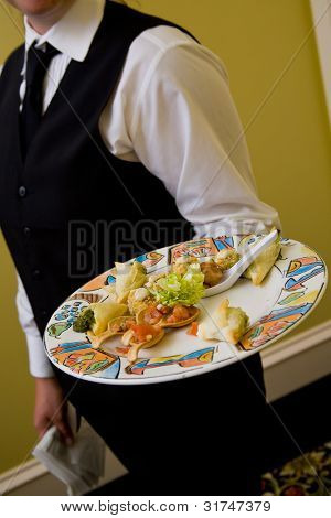 Appetizers being served by a waiter during a catered event
