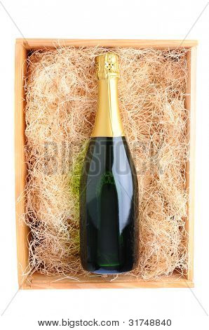 Overhead shot of a single champagne bottle in a wood shipping crate filled with packing straw. Vertical format over a white background