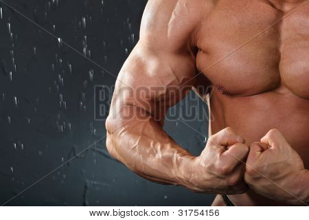 Undressed tanned bodybuilder stands and shows muscles in black studio