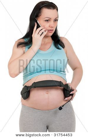 Pregnant with headphones - isolated over a white background. Third trimester.