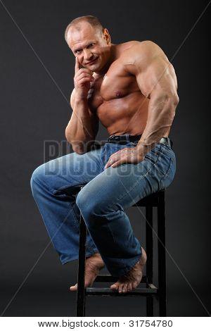 Sunburnt smiling bodybuilder wearing in jeans sits at stool inside black studio