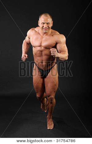 Undressed sunburnt smiling bodybuilder runs inside black studio