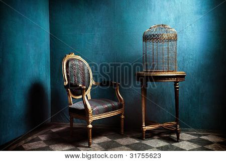Louis table, armchair and old golden bird cage in blue room with tiled floor