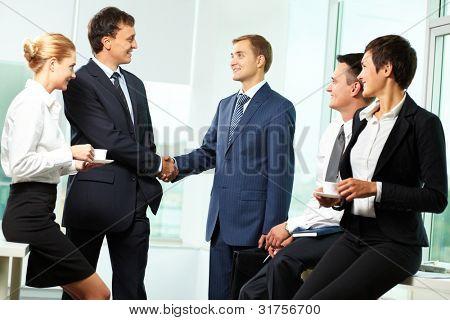 zwei Männer Händeschütteln und anderen Geschäftspartnern, die sie betrachten