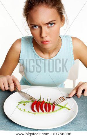 Porträt von frowning Mädchen mit Gabel und Messer in Händen und Platte mit red hot Chili Peppers vor