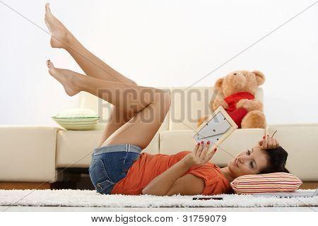 Happy young Girl zu Hause, im Erdgeschoss mit Blick auf Freund Foto, lächelnd.