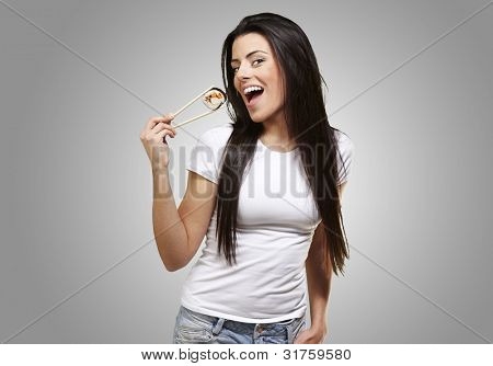 woman holding a sushi piece with chopsticks against a grey background