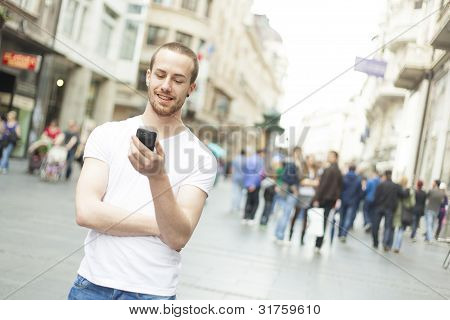 Young Man With Cell Phone Walking In City