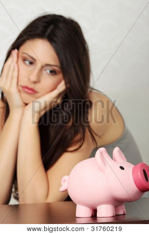 Finance - Young woman looking at piggy bank