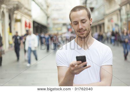junger Mann mit dem Handy gehen