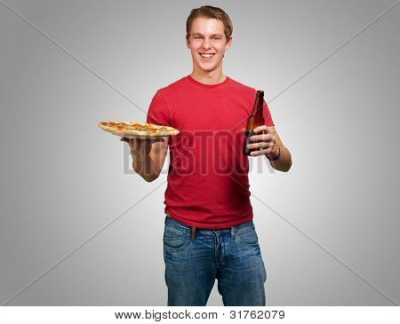 portrait of a young man holding a pizza and a beer over a grey background