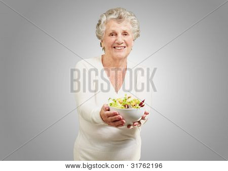 portrait of a senior woman showing a fresh salad over a grey background
