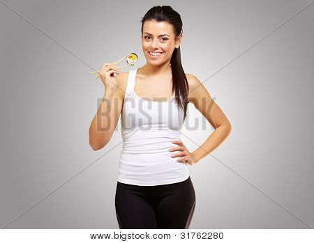young woman holding a piece of sushi with chopsticks against a grey background