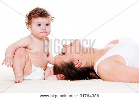Curly baby in diaper and her mother lying beside