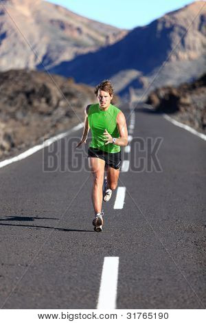 Running. Male athlete running training for marathon on beautiful mountain road. Man fitness sports model sprinting fast.